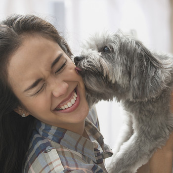 dog licking woman on the face as she smiles