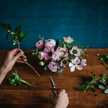 Person Arranging Flowers in a Low Vase