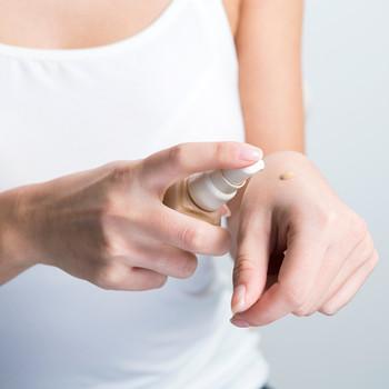 woman applying liquid foundation to wrist