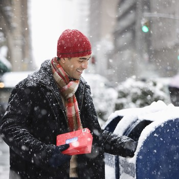 Man mailing Christmas cards in city