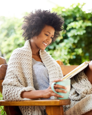 Woman Reading a Book Outdoors, Smiling