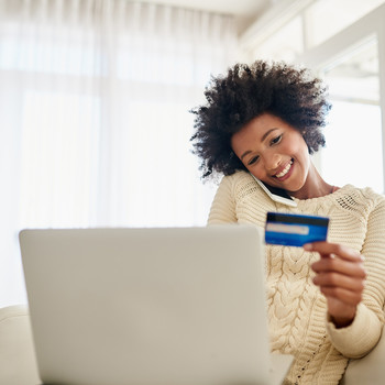 woman smiling with laptop holding credit card