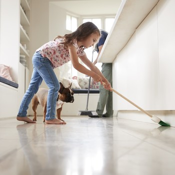 little girl cleaning the house with her dog