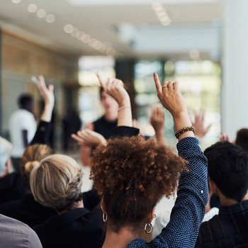 people raising their hands during meeting