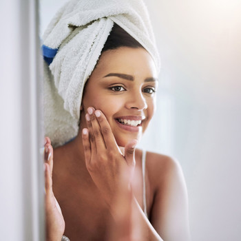 woman in towel touching face