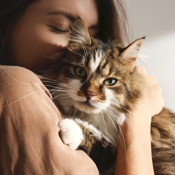 woman cuddling her tabby cat