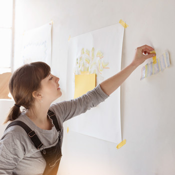 woman taping paper on wall