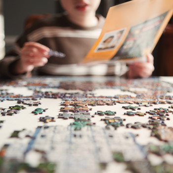 child working on jigsaw puzzle at table