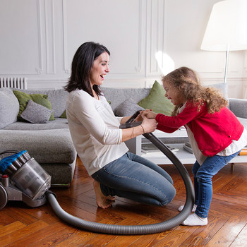 woman and daughter cleaning with vacuum