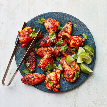 Quick Harissa Chicken Wings on blue board with tongs