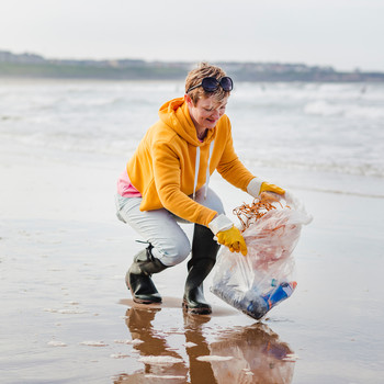 Woman Cleaning Trash of the Beach Shoreline