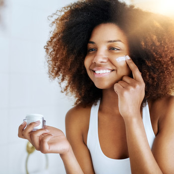 woman with curly hair using skincare