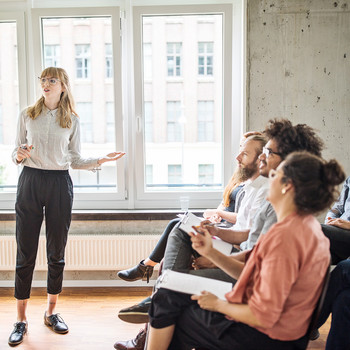 woman giving presentation in front of coworkers