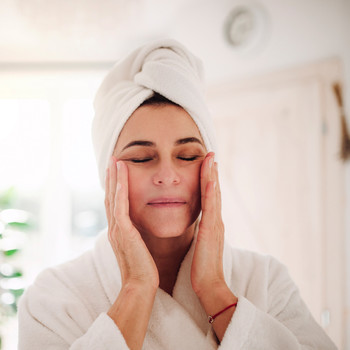 person with towel wrapped hair wearing white robe touching face