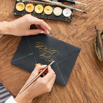 woman writing calligraphy on black envelope