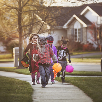 children trick-or-treating in Halloween costumes outdoors