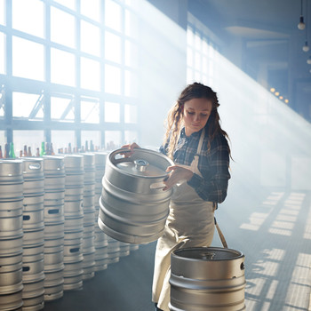 woman holding keg in microbrewery