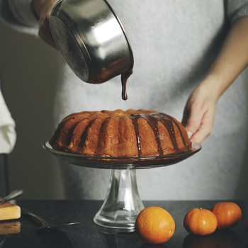Woman pouring melted chocolate on citrus cake