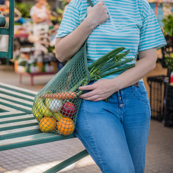 person standing with reusable green shopping bag
