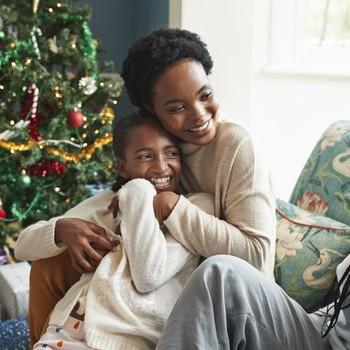 smiling woman embracing girl while sitting on sofa