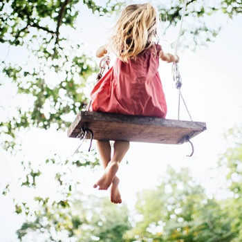 girl swinging playing outside