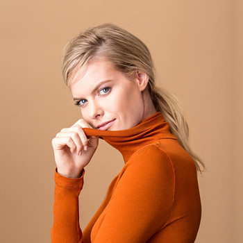 blonde woman wearing orange turtleneck