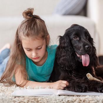 女孩躺在地上和狗一起看书