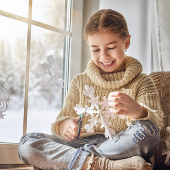child smiling while making paper snowflakes