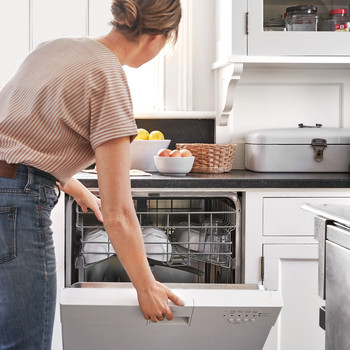woman closing dishwasher in kitchen