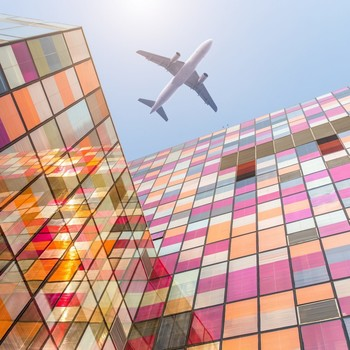 airplane flying over mosaic glass buildings