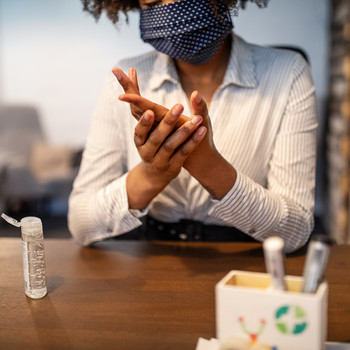 businesswoman wearing protective mask and sitting at her desk cleaning hands with sanitizer
