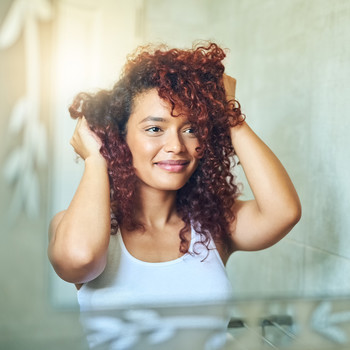 woman looking in mirror and touching her curly hair