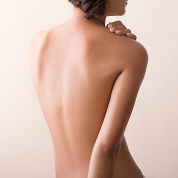 dry skin woman rubbing bare shoulder