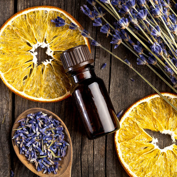 Essential oil bottle with orange slices and lavendar