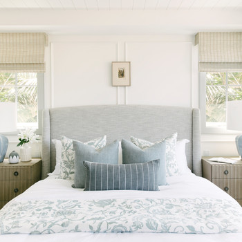 master bedroom blue-gray and white patterned bedding with double nightstand and lamp sets