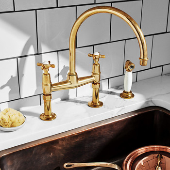 unlacquered brass faucet and sink with copper pot
