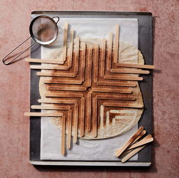 popsicle stick stencil art with sprinkled cinnamon sugar on pie crust