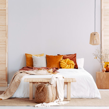 neutral-colored bedroom with orange decor