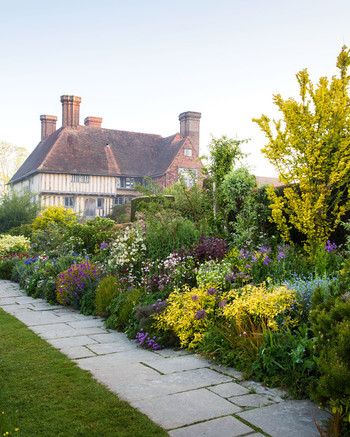 wall of flowers and stone path leading to english home