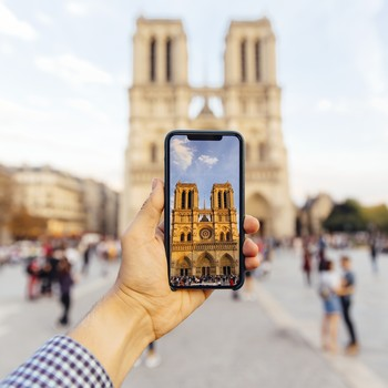 tourist photographing Notre Dame cathedral