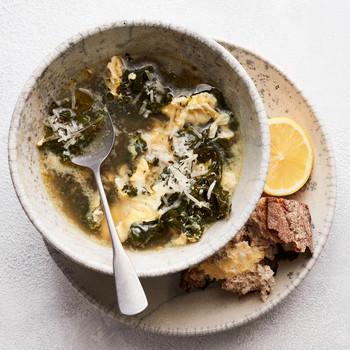 用灰色的碗盛着甘蓝和柠檬的意式脆片汤,旁边放着面包和柠檬
