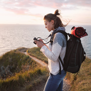 person on ocean cliffside wearing backpack looking at camera