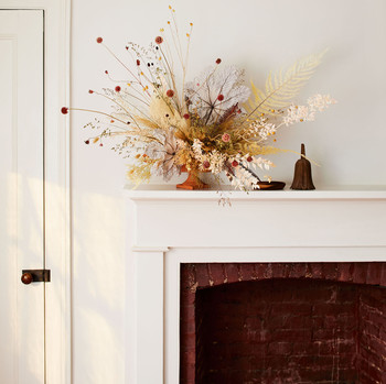 vase of dried flowers displayed on a white mantel