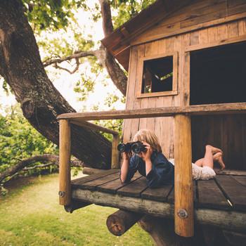 little boy in treehouse