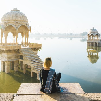 young woman looks out at Gadi Sagar lake in morning light