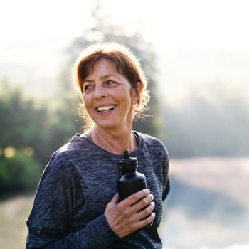 woman outside holding water bottle
