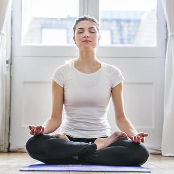 brunette woman meditating on yoga mat