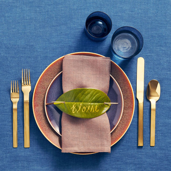earthy metallic accents and leaf placecard on place setting