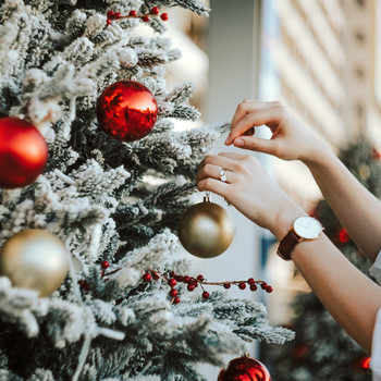 Woman Decorating Christmas Tree Outdoors