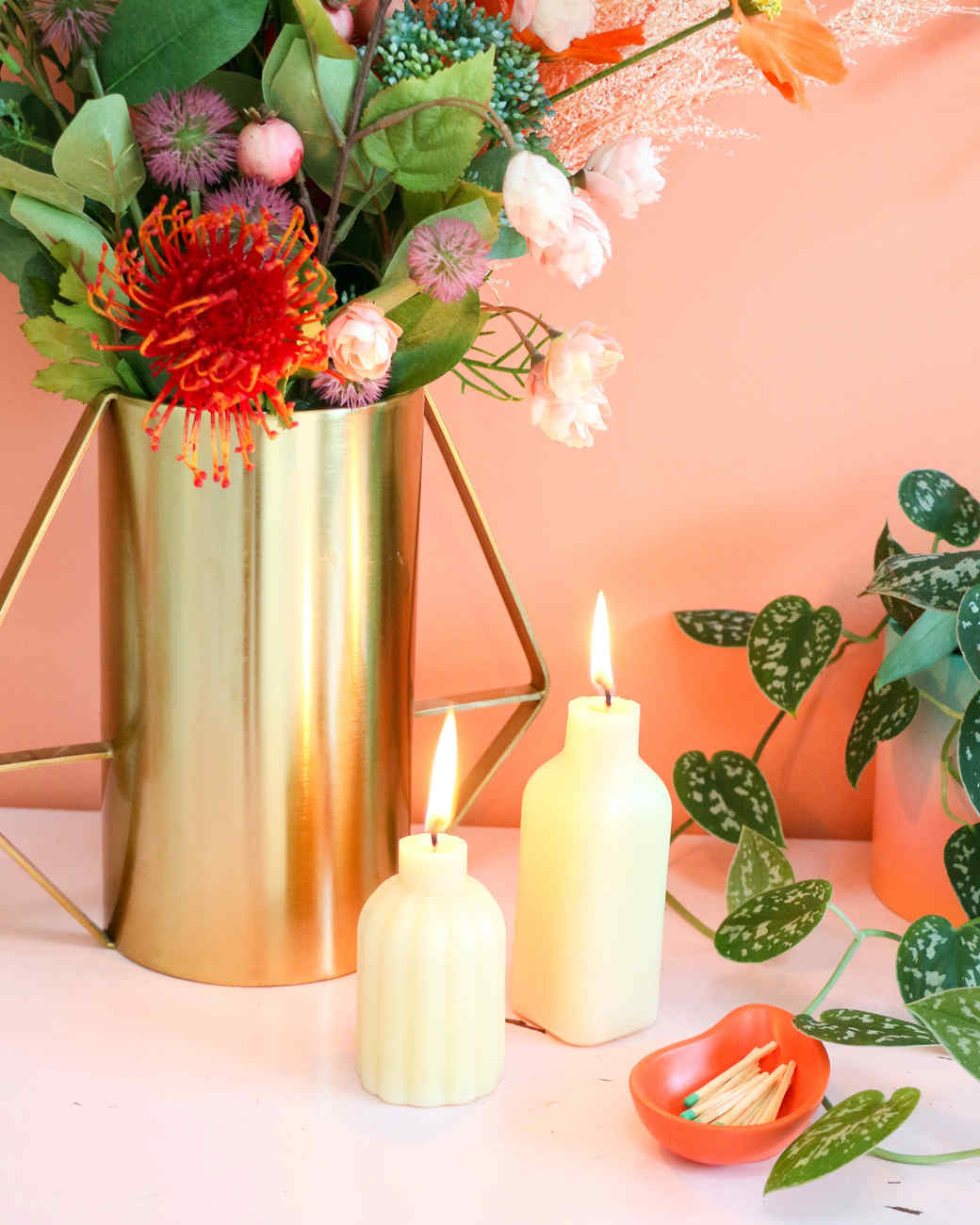 two white bottle candles lit and vase of flowers